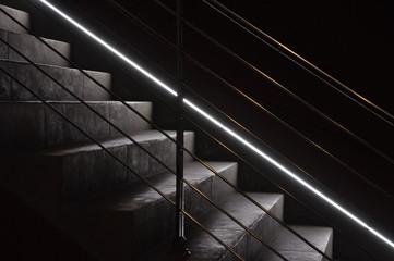 wenig beleuchtete Treppnstufen in Beton in der Dnkelhiet mit schmalem Lichtband