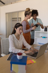 Female executive using laptop while coworkers discussing over digital camera