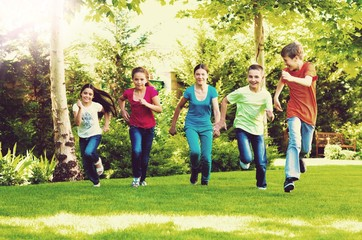 Happy  children running and playing in garden on sunny day Wall mural