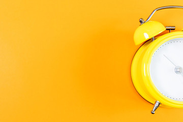 Alarm clock without numbers on a bright orange background, top view. Background image, minimalism, place for text.