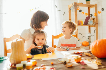 family mother and child daughter in hat witch are preparing for Halloween carve a pumpkin and decorate the house Happy Halloween concept Wall mural