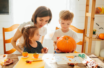 Happy Halloween. Attractive young woman with her little cute kids are preparing to Halloween on kitchen having fun with pumpkins. Happy Halloween concept Wall mural