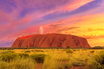 Amazing dramatic colorful sunset sky over Ayers Rock in Uluru-Kata Tjuta National Park - at Living Cultural Landscape, Australia, Northern Territory. Majestic australian outback or Red Center