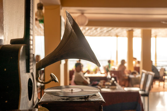 Old gramophone, guitar and people in restaurant, focus on gramophone, closeup