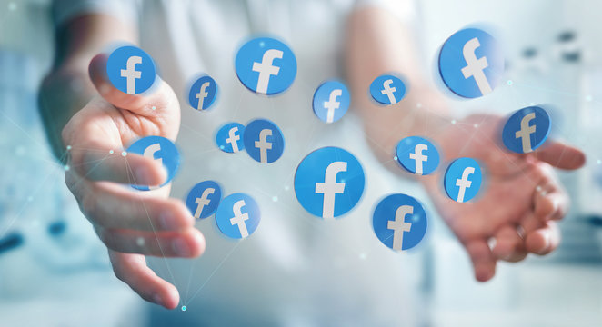 PARIS, FRANCE – SEPTEMBER 16, 2019: Man with floating Facebook new logo between his hands and digital connections. 3D rendering