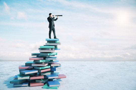 Career growth and development concept with businessman on book mountain looking through a telescope.
