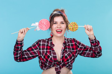 Pretty smiling young woman in a plaid shirt closes her eyes with big colorful lollipops and posing against a blue background. Concept of fun and desserts.