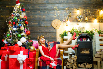 Woman in Christmas dress near the Christmas tree. Colorful makeup and retro hairstyle for Christmas or new year party. Beautiful pinup girl with Christmas pin-up makeup holding glass of champagne.
