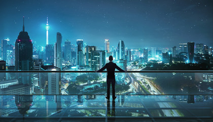 Businessman standing at transparent glass floor on rooftop with night city panoramic view.