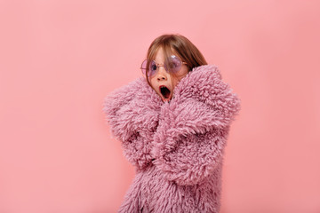 Close up portrait of lovely funny little girl wearing round violet glasses and stylish fur coat cover face with hands