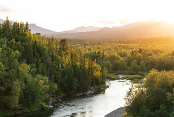 Fototapete - The sun setting over a river in a   mountain wilderness.  Jamtland, Sweden.