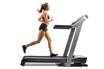 Young sporty female athlete running on a treadmill