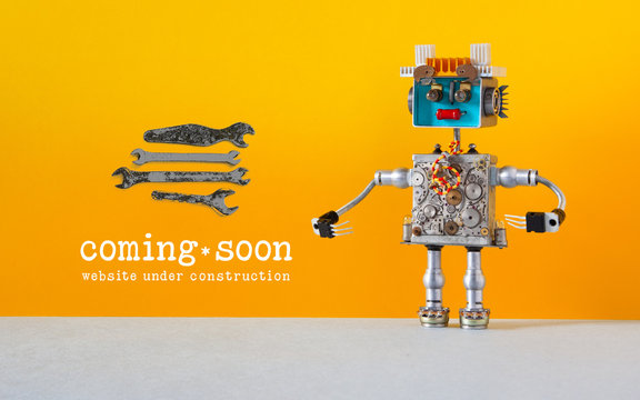 Web site under construction Coming Soon template page. Toy robot looks at a set of hand wrenches for maintenance repairs and service works. Orange wall and copy space on gray background.
