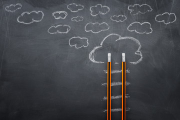 Education concept of Ladder made from pencils next to clouds over blackboard