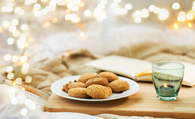 Fototapete - food, bakery and hygge concept - oatmeal cookies on plate and candle in holder at home