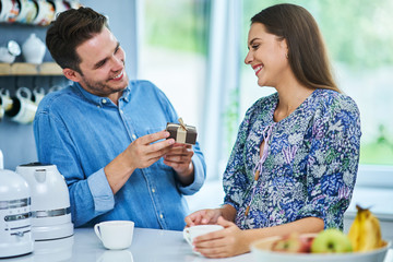 Adult man giving present to his wife in the kitchen