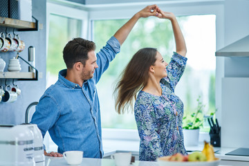 Adult couple dancing in the kitchen