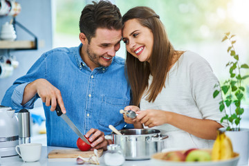 Adult couple cooking together at home