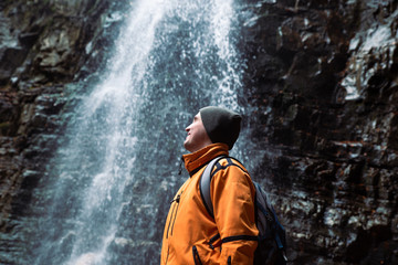 man hiking concept looking at waterfall in dip forest