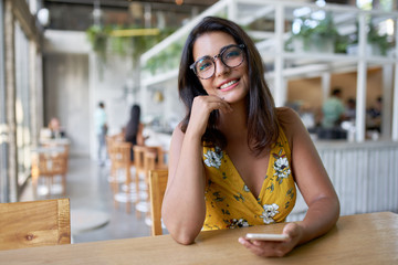 Lifestyle portait of confident beautiful natural brunette hispanic millennial vlogger sitting in modern restaurant smiling at camera