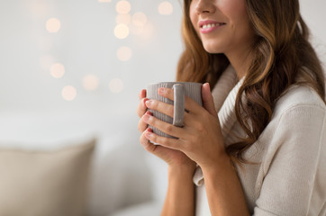 Fototapete - drink, christmas and hygge concept - close up of happy woman with cup of coffee or tea at home