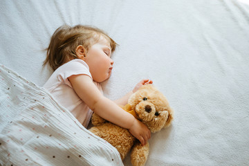 Little baby sleeping on bed embracing soft toy, free space