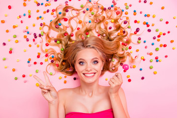 Close up top above high angle view photo beautiful she her lady show v-sign lying down sweets ideal hair colored little candies trying lolly pop wearing classy chic dress isolated pink background