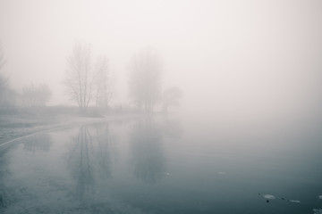 Dreamy river bank with trees and reflections in the water at foggy autumn morning. Fototapete