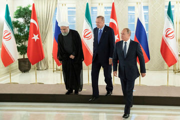 Presidents Hassan Rouhani of Iran, Tayyip Erdogan of Turkey and Vladimir Putin of Russia walk after a group picture during their meeting in Ankara