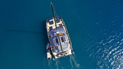 Aerial drone top down photo of luxury Catamaran sail boat docked in Mediterranean popular Aegean destination port with deep blue sea