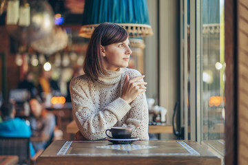 Beautiful young woman in warm sweater in the cafe near the window with coffee. Cozy autumn or...