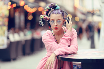 Young woman listening to music via headphones on the street - Hipster Girl with a nonconformist fashion look