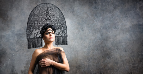 Young sexy woman brunette in stylish neofolk black kokoshnik stands on stone backgrount Wall mural
