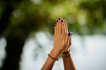 Picture of female`s hands in praying position. Yoga exercising in nature concept.