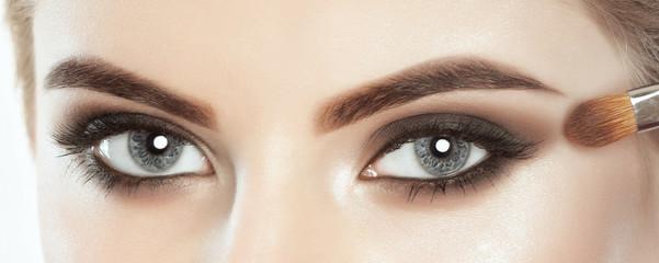 Beautiful woman with long eyelashes and with beautifulsmokey eyes make-up. Looking at the camera