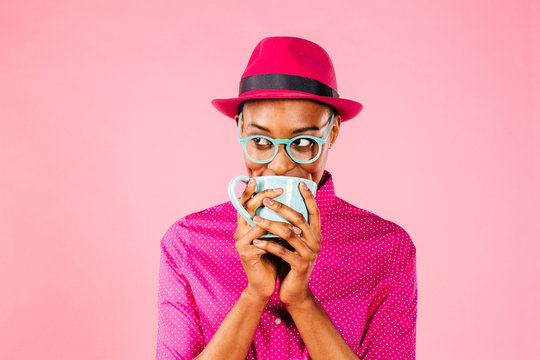 Portrait of a smart young woman with glasses drinking a coffee mug and looking to side, isolated on pink studio background.