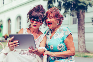 Two excited senior women sitting in outdoor cafe laughing and watching funny videos on a tablet