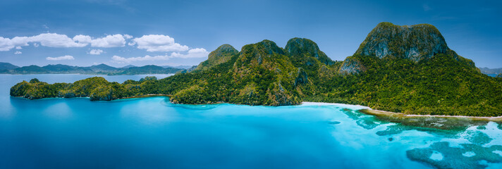 Foto auf Leinwand Insel Aerial drone panoramic view of uninhabited tropical island with rugged mountains, rainforest jungle, sandy beaches surrounded by blue ocean