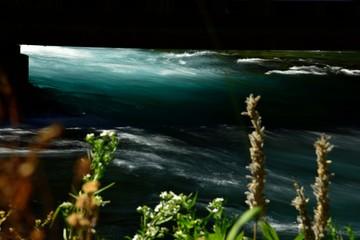 Metolius River flows under a bridge near Camp Sherman, Oregon.  Long exposure to highlight the flow.