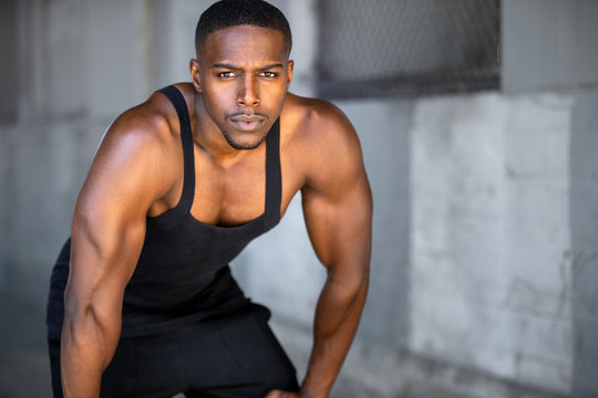 Portrait of african american athlete, urban fitness exercise and training, staring at camera with intense eyes