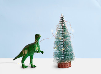 Funny green Tyrannosaur Rex with lights decorating pine tree. Minimal Wall mural