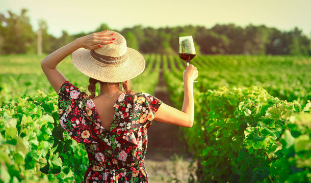 Asian woman drinking red wine at vineyard during her vacation