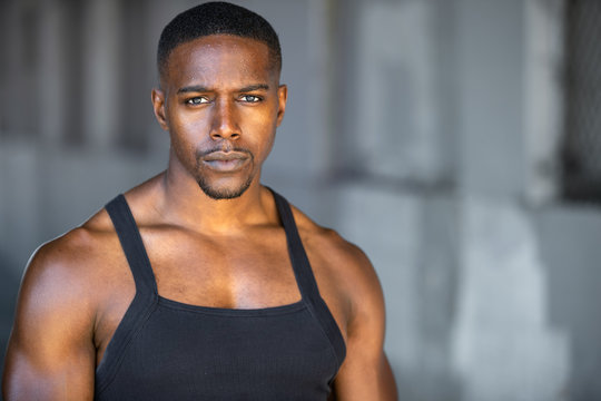 African american fitness and sport head shot portrait in tank top in gritty urban concrete background with copy space