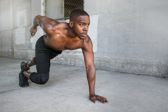 Shirtless male african american athlete training in urban city concrete background, sprinter, runner, jogger, muscular toned build training for race