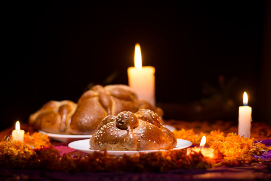 Pan de Muerto traditional recipe from Mexico, adorned with candles and cempasuchil flower petals, in the diffuse background, commemorating the Day of the Dead.