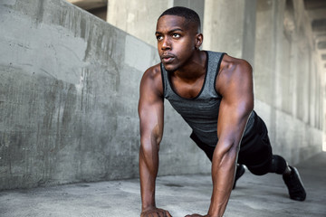 Muscular strong male athlete strength training and fitness in city setting on concrete