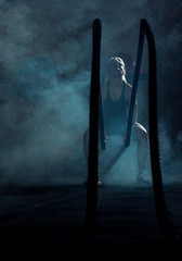 Determinated woman tossing ropes at gym, low key, dark image