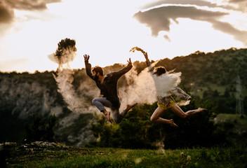 Happy romantic couple dancing open air under sunset sky