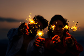 Picture showing young silhouette couple having fun with sparklers, low key, dark image