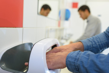 closeup of male hands in contactless air hand dryer